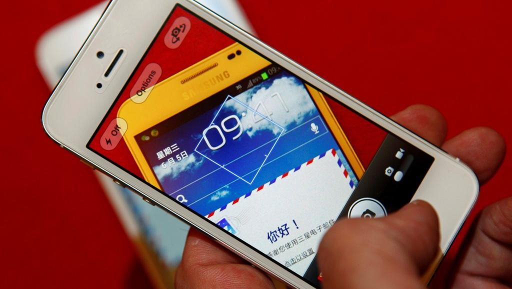 A man uses an iPhone 5 to take a picture of a Samsung Galaxy Note smartphone in this file photo illustration taken in Beijing June 5, 2013.